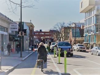 A woman bikes on the two-way protected bike lane on Brattle Street
