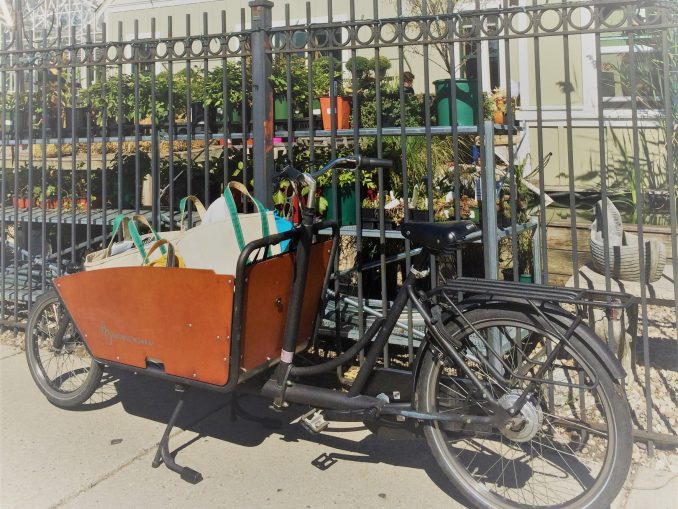 A cargo bike with a large wooden box in the front, filled with groceries, in front of a metal fence with plants in the background.